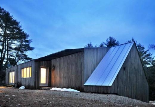 Moderna cabaña de madera en el bosque canadiense